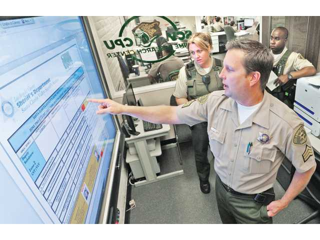 Los Angeles County sheriff's Sgt. Marcy Marder, left, and Deputy Sylvester Hardison, right, observe as Sgt. Darren Harris, center, displays a zone crime briefing report on the SMART Board in the crime research center in the Santa Clarita Valley Sheriff's Station in Valencia.