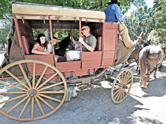 Caitlyn Jones (8), left, and brother Brady (10) of Valencia hitch a ride in a replica 1800's stage coach at the inaugural SCV Wild West Days at Heritage Junction in Newhall on Saturday.