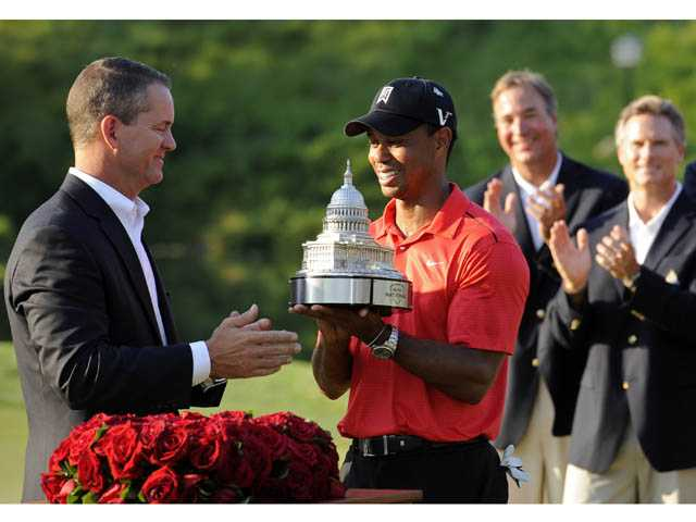 Tiger Woods, center, receives the trophy from Rob Forsyth, AT&T Mobility vice president and general manager, after winning the AT&T National golf tournament at Congressional Country Club in Bethesda, Md., on Sunday.