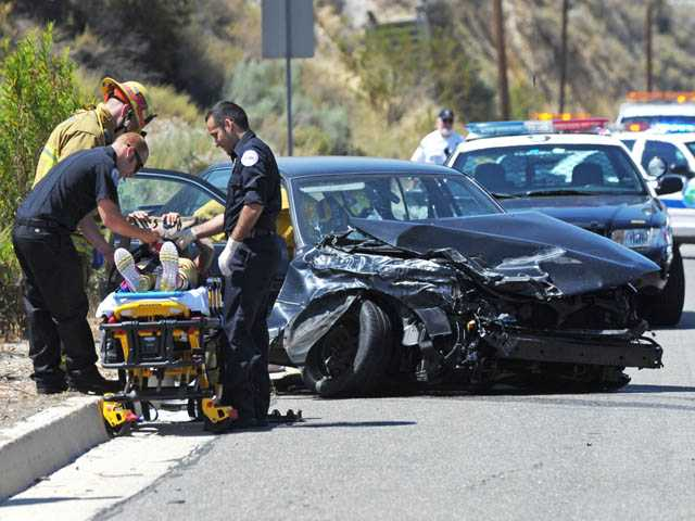 Emergency medical technicians prepare to transport a female patient away from a Toyota Camry involved in a collision with a Honda Pilot on Sierra Highway north of Placerita Canyon Road in Newhall on Monday.