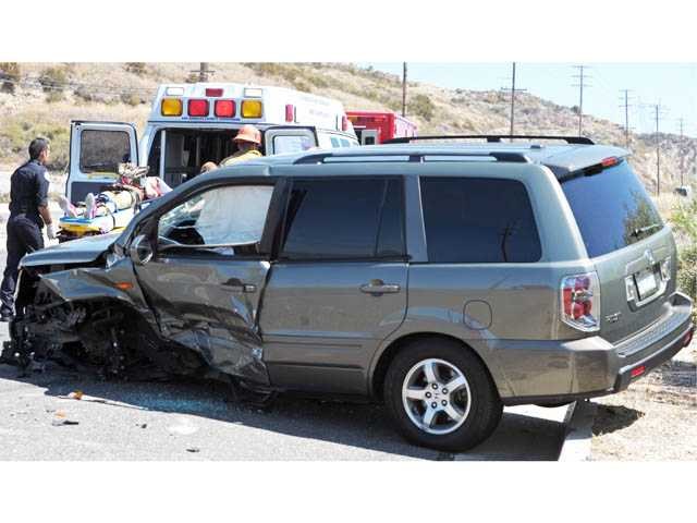A female patient is taken to an ambulance behind a Honda Pilot involved in a collision with a Toyota Camry on Sierra Highway north of Placerita Canyon Road in Newhall on Monday.