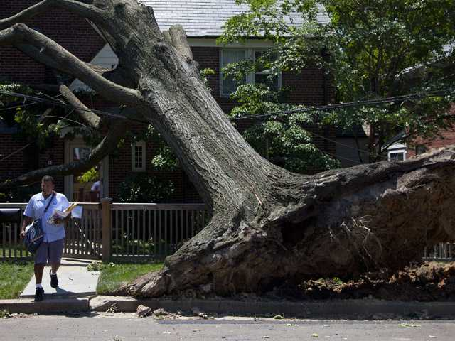 Giovanny Alvarez, a letter carrier for the U.S. Postal Service, leaves after delivering mail to a residence in Washington, Monday, July 2, 2012, damaged by the powerful storm that swept through the region Friday.