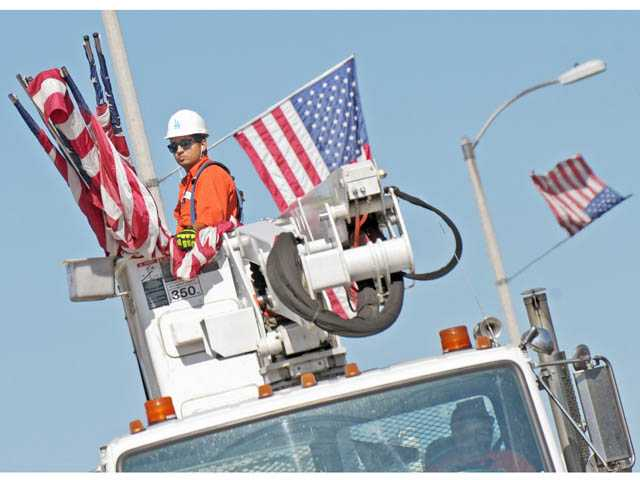 City workers install American flags on light poles in Lyons Avenue in Newhall on Monday.