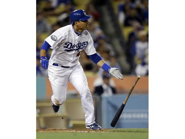 Los Angeles Dodgers' Luis Cruz watches his RBI-double against the Cincinnati Reds during the seventh inning of a baseball game in Los Angeles, Tuesday, July 3, 2012. (AP Photo/Chris Carlson)