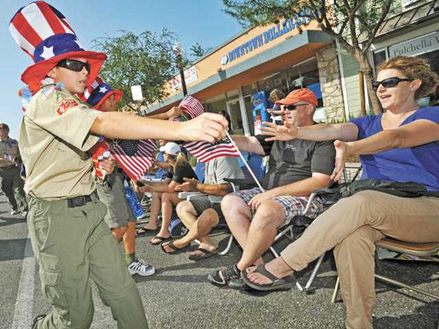 Boy Scout Zach Cashin hands out American flags along Main Street during the Santa Clarita 4th of July Parade in Newhall on Wednesday.