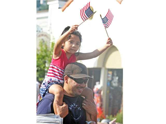 Kiana Funakoshi, 4, waves flags as her father, Mark Funakoshi, carries her down Main Street during the Santa Clarita Fourth of July Parade in Newhall on Wednesday.