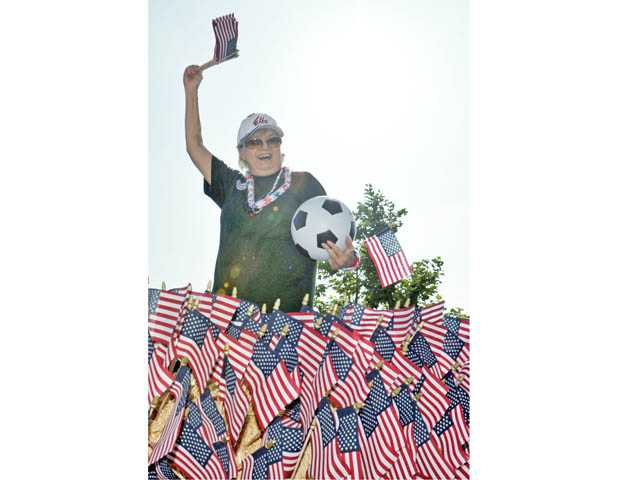Donna DiMarco waves to the crowd on board the Elks Lodge float during the Santa Clarita Fourth of July Parad.