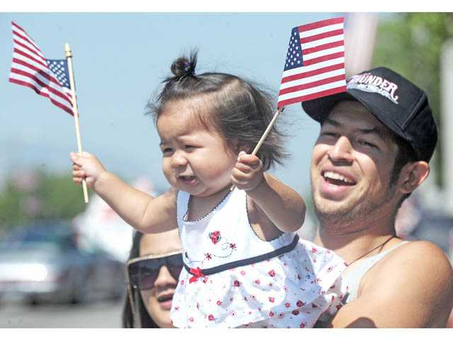 Kailyn Rosales, 1, and father Steve Rosales enjoy the Santa Clarita Fourth of July Parade along Lyons Avenue in Newhall on Wednesday.