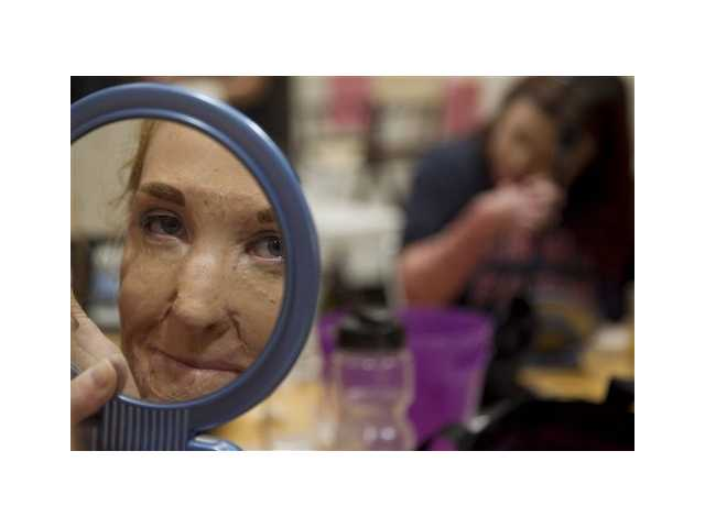 In this June 22, 2012, photo, Anastaza Pack, 17, looks in the mirror as she puts on make-up at the Angel Faces retreat in Corona, Calif. Angel Faces is an annual retreat for young girls with severe burns or facial disfigurement that focuses on psychological healing