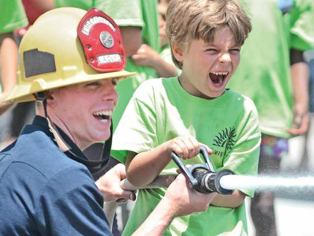 Firefighter Brian Noss, left, assists Enzo Lovara, 6, as he sprays a hose during a demonstration at the SCV Tutors CARE Learning Academy in Santa Clarita on Thursday.