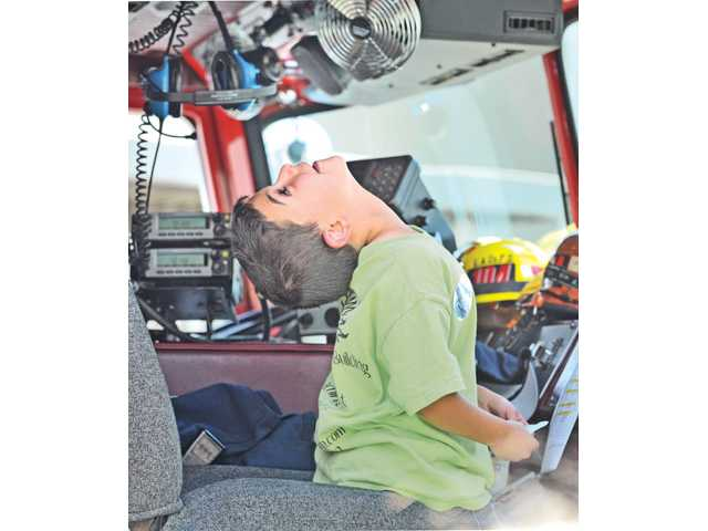 Alex Ivanoff, 8, cranes his neck as he gets a close-up look of the equipment in the cab of a water-pumping ladder truck.