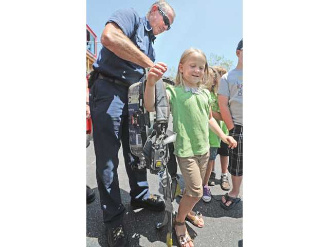 Firefighter Jon Maass, left, helps Lillie Robinson, 5, try on equipment at the SCV Tutors CARE Learning Academy in Santa Clarita on Thursday.