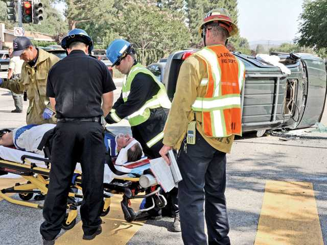 Emergency medical technicians treat a man involved in a rollover crash on Seco Canyon Road at Guadilamar Drive in Saugus on Thursday.