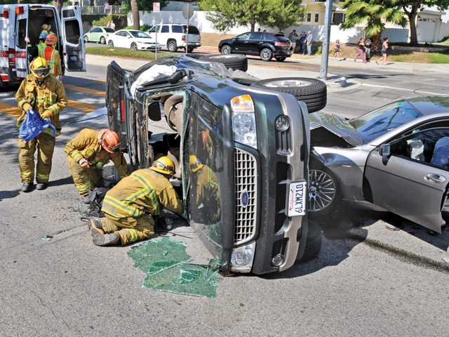 Firefighters work the scene of a rollover crash on Seco Canyon Road at Guadilamar Drive in Saugus on Thursday.