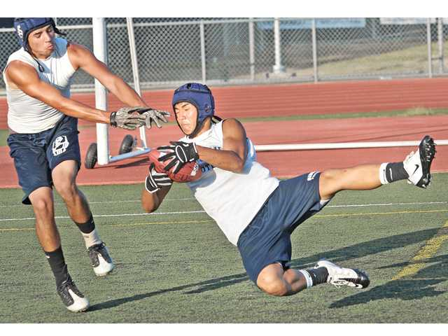 Kevin Lee, 16, of Saugus High, catches a touchdown pass in the end zone against Sylmar defender Daniel Mendoza at Canyon High Thursday.