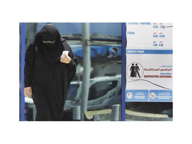 A muslim Emirati woman passes by a dress code sign at a shopping mall in Dubai, United Arab Emirates.