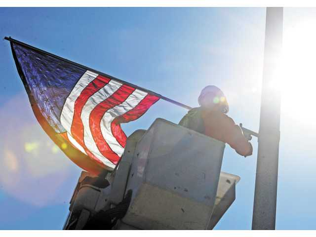 A city worker installs an American flag on a light pole on Lyons Avenue in Newhall on Monday.