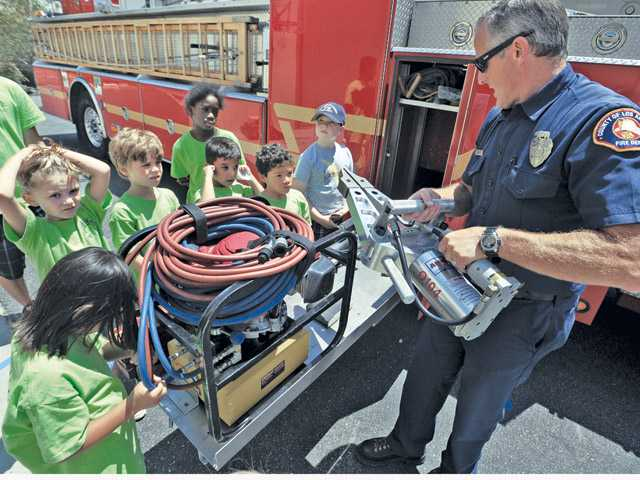 Engineer Jon Maass, right, demonstrates how firefighters use the jaws of life to campers of the SCV Tutors CARE Learning Academy in Santa Clarita on Thursday.
