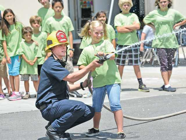 Firefighter Brian Noss, left, assists Caroline Lawton, 10, as she sprays water from a fire hose. The visit was part of the camp's Hero Week.