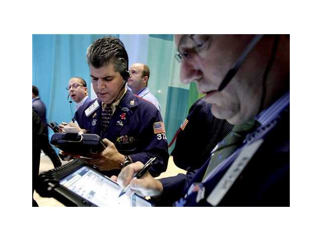 Traders work on the floor of the New York Stock Exchange. Stocks dropped sharply on Wall Street, Friday,
