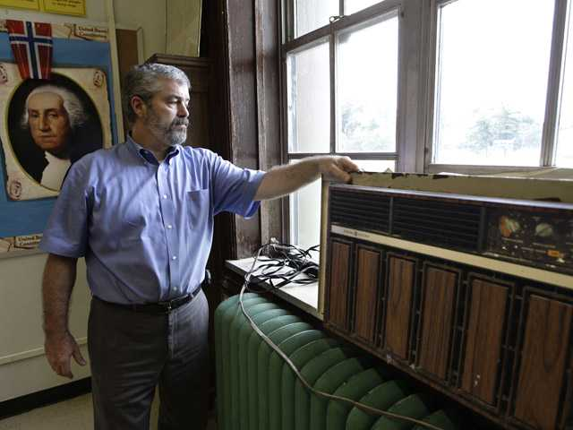 In this Thursday photo, John Carr, who heads up the facilities department of the Yonkers Public Schools, points out a decades-old window air conditioner installed in one of the classrooms at the 88-year-old Charles E. Gorton High School in Yonkers, N.Y