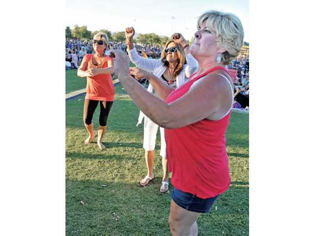 Saugus residents, from left, Annie Estes, Rose Di Benedetto, and Shannon Donathan dance at the first of the Concerts in the Park at Central Park in Saugus on Saturday.