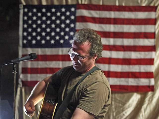 In this June 7 photo, Jason Moon, a veteran and singer-songwriter, performs during his concert in Glendale.