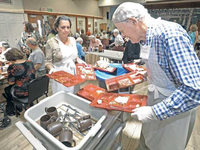 Volunteers Dana Blackman, left, and Edwin Polinsky clean trays from tables after lunch at the Santa Clarita Valley Senior Center recently in Newhall.