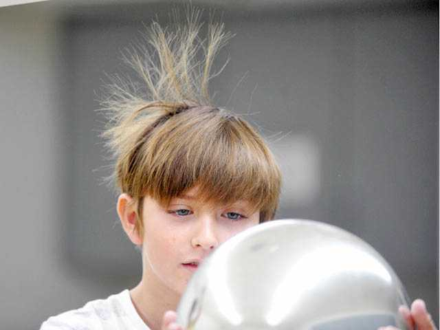 Static electricity from a Van de Graaff generator flows through Ethan Dempsey, 10, causing his hair to stand on end.