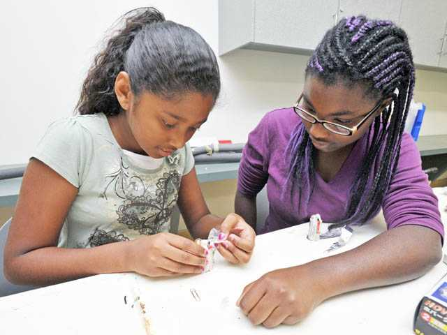 Amira Fann, 11, and Zoe Shaw build a flashlight.