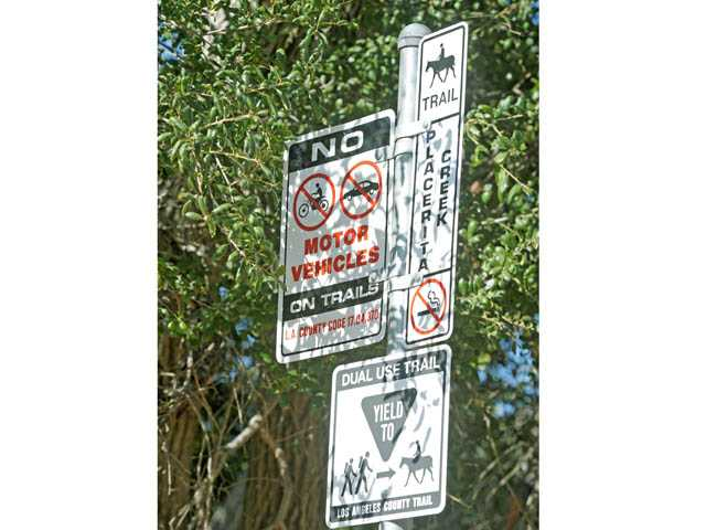Signage is seen at the head of Canyon Trail in Newhall on Monday.