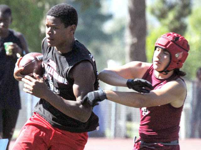 Hart receiver Kaiser Butler runs the ball as Santa Paula cornerback Justin Gaeta defends at a passing camp on Monday at College of the Canyons.