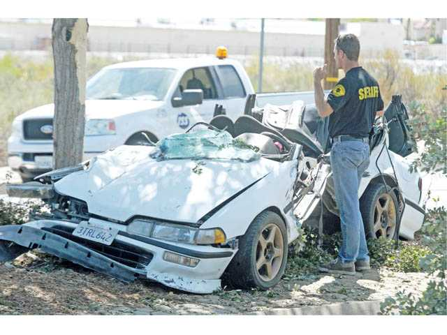 A sheriff's investigator works the scene of a fatal crash on Soledad Canyon Road west of Camp Plenty Road in Canyon Country on Tuesday morning.