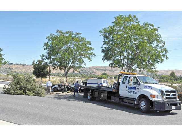 Tow truck drivers prepare to move a car involved in a fatal crash on Soledad Canyon Road west of Camp Plenty Road in Canyon Country on Tuesday.