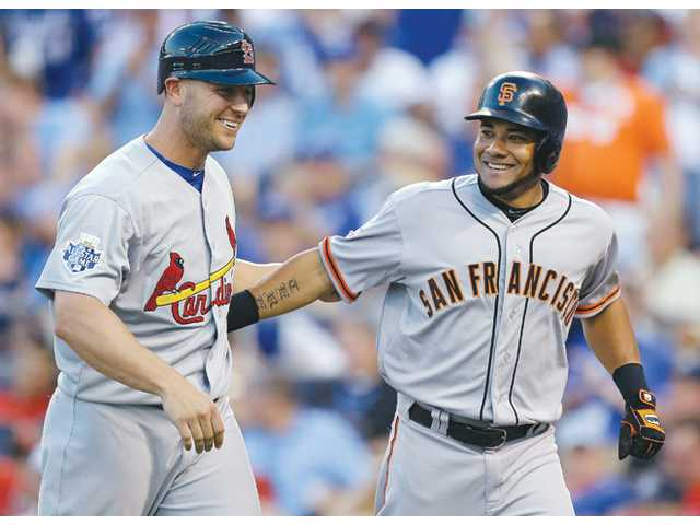 National League's Melky Cabrera, right, of the San Francisco Giants, celebrates his two-run home on Tuesday in Kansas City, Mo.