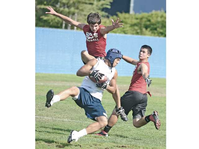 Saugus High's Kevin Lee, center, comes down with a pass against Santa Clarita Christian School defenders Sheppard Smith, left, and Jacob Nogle on Tuesday at COC.