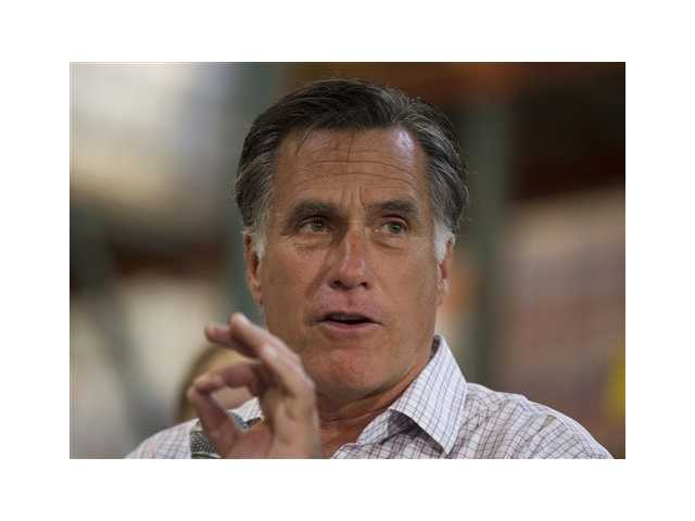 Republican presidential candidate, former Massachusetts Gov. Mitt Romney gestures during remarks to volunteers working at the Care and Share Food Bank of Southern Colorado