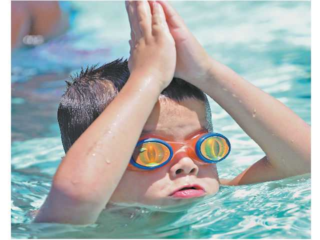 Ethan Charon, 4, of Newhall, pretends to be a shark as he cools off in 100-plus degree heat at the Newhall Park Community Pool in Newhall on Tuesday.