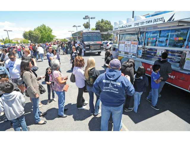 People line up for food from gourmet food trucks at the 2011 Gourmet Food Truck Fest and Classic Car Show.