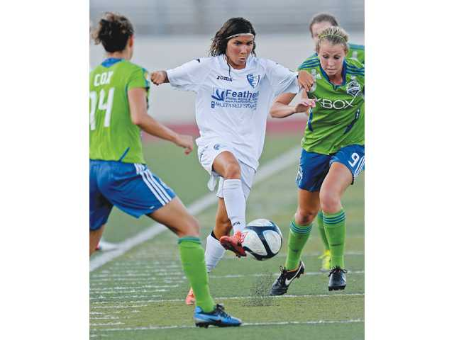Santa Clarita Blue Heat player Ana Borges, center, takes the ball through Seattle Sounders Stephanie Cox, left, and Julia Roberts in the first half a United Soccer League W-League game on Wednesday at Valencia High School.