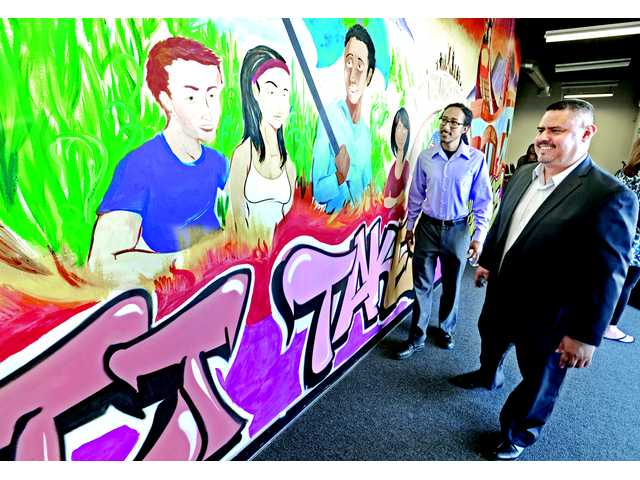 Action Family Zone Director Alex Urbina, right, and artist Peter Marquez discuss Marquez's mural displayed at the grand opening of the new Action Family Zone facility in Canyon Country.