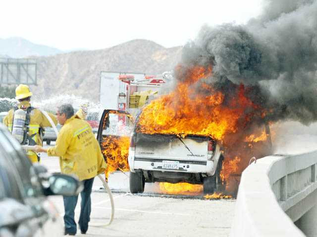 Firefighters arrive to knock down a fully engulfed Chevrolet Blazer on the shoulder of northbound Interstate 5 near the Magic Mountain Parkway on-ramp in Valencia on Friday.