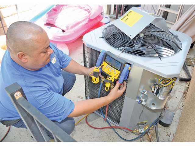 Air-conditioning Installer Sergio Vilega with Santa Clarita Custom Air charges the lines of a home air-conditioning system with nitrogen to check the system for leaks. (Right) Vilega braises the copper suction line during an AC installation.