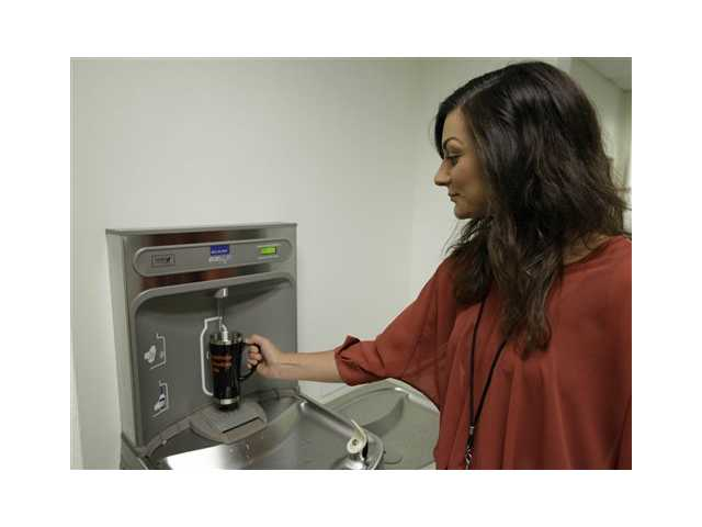 Shauna Barbera uses a bottled water dispenser at the California Institute of Integral Studies in San Francisco.