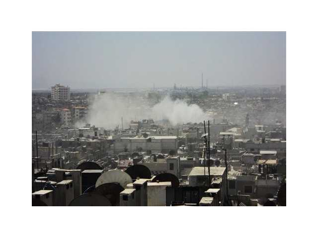 Smoke leaps the air from purported forces shelling in Homs, Syria.
