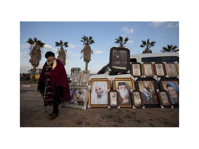 A Jewish woman stands next to pictures of rabbis for sale near the tomb of the Baba Sali, Rabbi Yisrael Abuhatzeira, during the annual pilgrimage to his grave on the 28th anniversary of his death.