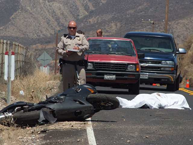 A California Highway Patrol officer works the scene of a fatal motorcycle crash on Soledad Canyon Road near Highway 14 on Saturday afternoon.