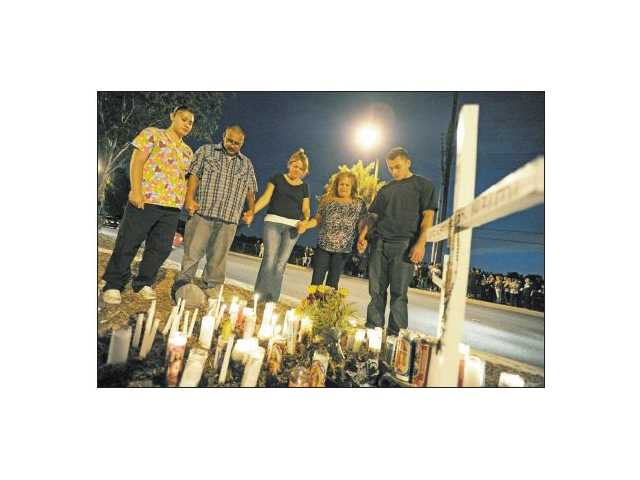 Close friends of Luis Castillo pray around a memorial in Canyon Country on Friday at the spot where he was killed in a crash. From left, Mayra Prial, Gregorio Prial, Denise Reeves, Dory Aase and David Aase.