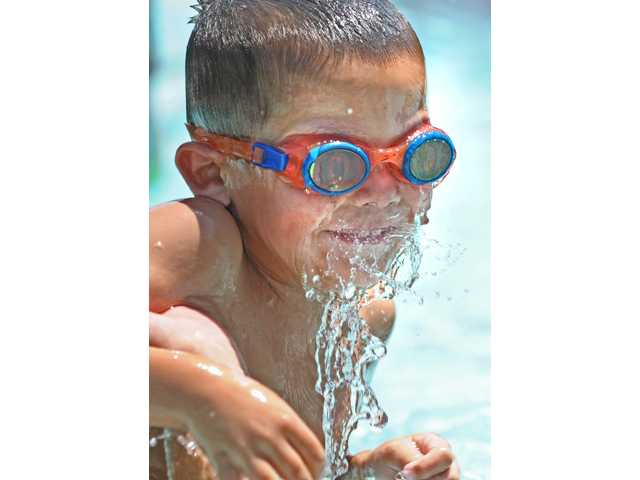 Ethan Charon, 4, of Newhall, cools off in 100-plus degree heat at the Newhall Park Community Pool on Tuesday. The pool  is located at 24907 Newhall Avenue in Newhall and open to the public for recreational swimming,   12:15-4 p.m. Monday through Friday.