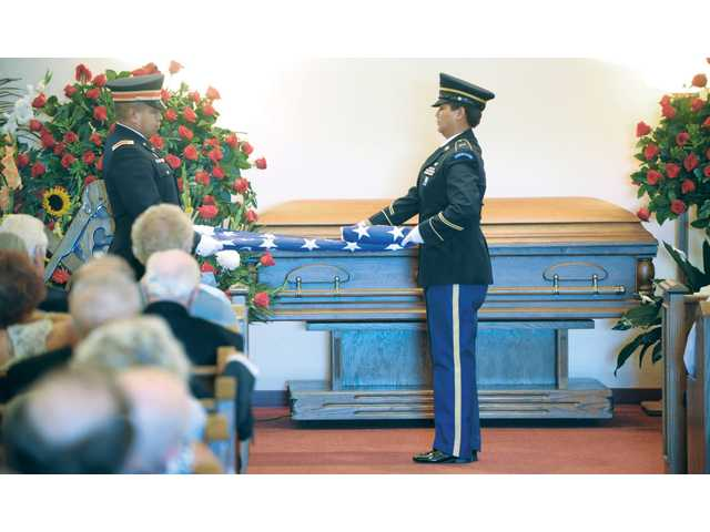 The American flag is removed and folded from the casket of Harry Bell at the funeral in Newhall on Saturday. Click here for more photos.